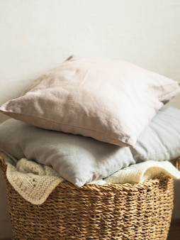 Wicker basket with a white soft knitted blanket and gray cushions against a white wall