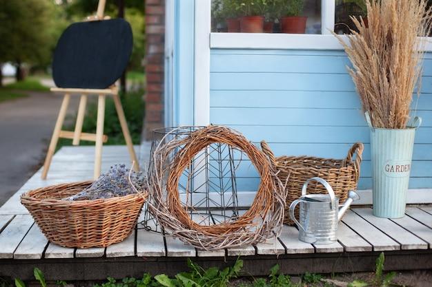 園芸工具の横にある籐のバスケット、じょうろ、乾燥した小穂、青い家の壁にススキ。庭の居心地の良い装飾