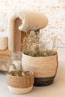 Wicker baskets with dried flowers near the sofa