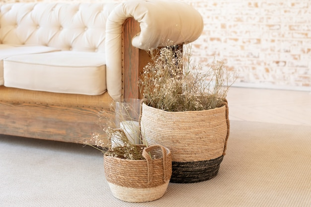 Wicker baskets with dried flowersnear the sofa on floor