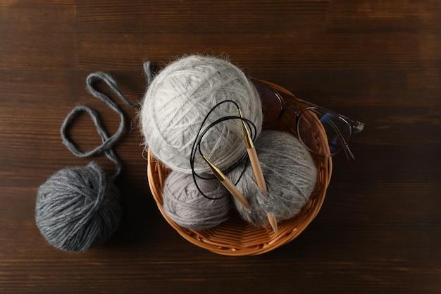 Плетеная чаша с шариками пряжи и спицами и очками на деревянном фоне