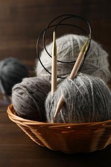 Плетеная чаша с шариками пряжи и спицами на деревянном фоне