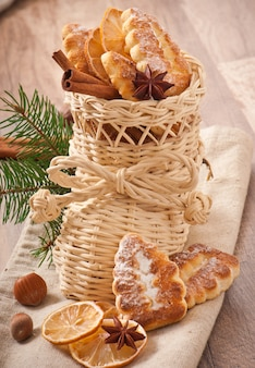 Wicker christmas stocking filled with cookies, cinnamon sticks, candied lemon and star anise