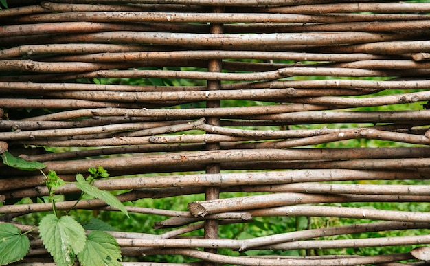 Wicker fence of willow branches. rustic fence