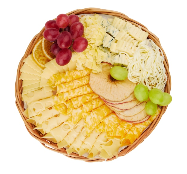 Wicker flat basket with a delicious assortment of cheese, dried orange slices, dried apples, grapes isolated on a white background