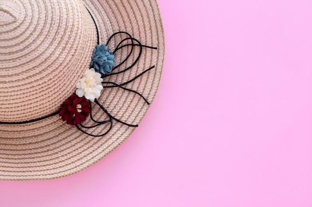 ピンクの背景に籐の帽子