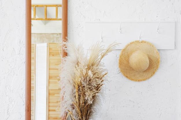 ミニマルなインテリアの白い木製ハンガーに籐の帽子。プロバンスのコテージの廊下にある鏡と乾いた小穂の花束。