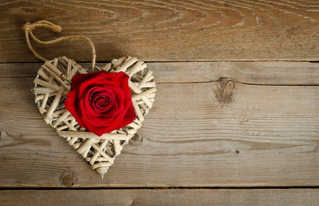 Wicker heart handmade with bud of red rose