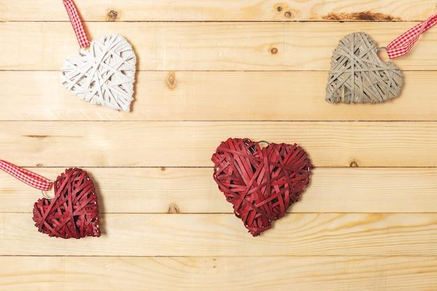 木製の背景にわらで作られた籐の心