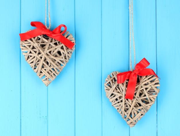 木製の背景に赤い弓と枝編み細工品の心