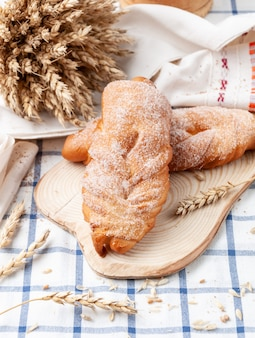 Wicker homemade bun sprinkled with sugar. on a wooden plate. white tablecloth in blue stripes. in the background, an ear of wheat and grain. country style