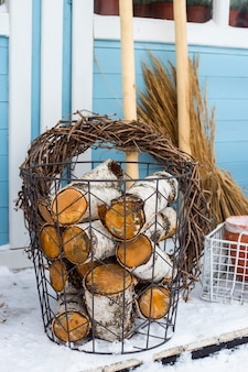 Wicker metal basket with birch wood next to the garden tools at the wall of a blue country house