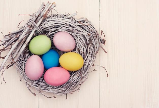 Wicker nest full of multi colored eggs