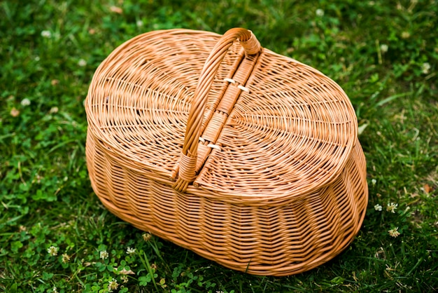 Wicker picnic basket on grass top view