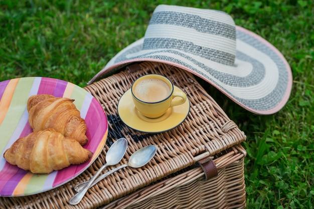食べ物とコーヒーと緑の草の上の枝編み細工品のピクニックバスケット。