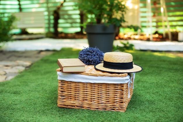 本と花束の花が付いている枝編み細工品のピクニックバスケット草の上のラベンダー芝生のピクニックランチ