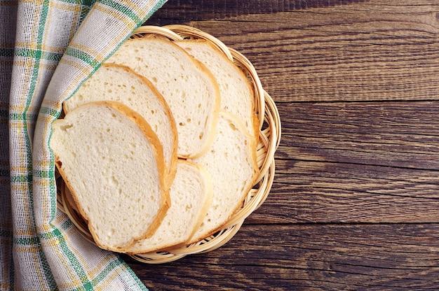 Плетеная тарелка с ломтиками белого хлеба на столе