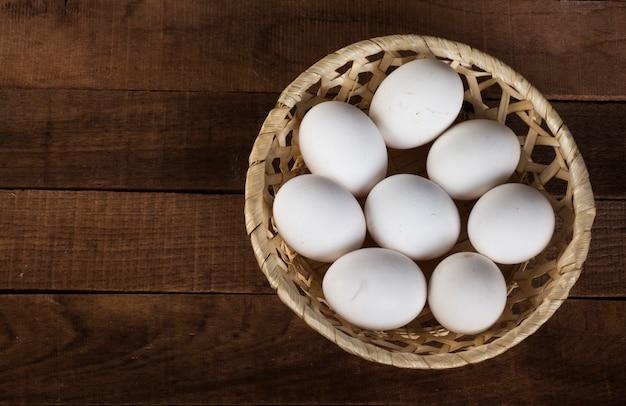 나무 갈색 배경, 공간의 복사본과 상위 뷰에 흰색 계란 고리 버들 세공 접시.