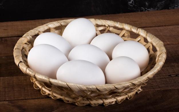 나무 갈색 배경에 흰색 계란 고리 버들 세공 플레이트.