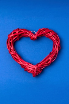 Wicker red heart on blue background. greeting card for a valentine's day. copy space, flat lay, top view.