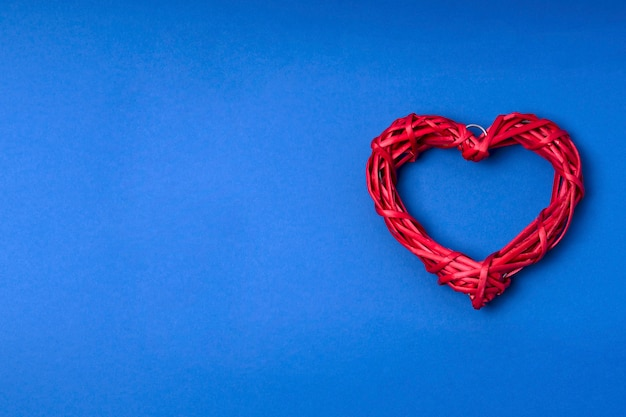 Wicker red heart on blue background.