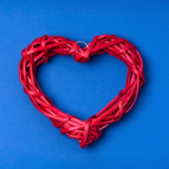 Wicker red heart on blue surface. flat lay, top view.