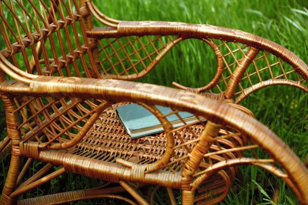 Плетеное кресло-качалка с книгой в саду