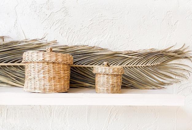 乾燥したヤシの葉が付いている白い棚の枝編み細工品のわらのバスケット。ミニマルなスカンジナビアのインテリア。