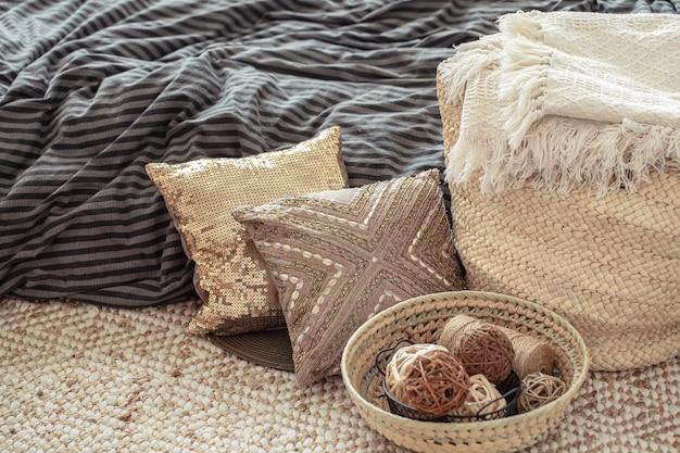 Grande borsa di paglia di vimini, cuscini ed elementi decorativi sullo sfondo del letto.