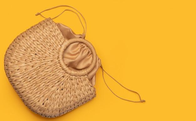 黄色の壁に細部の籐のストローまたは籐の女性用エコバッグ。フラット横たわっていたトップビュー。旅行夏の壁のコンセプトです。ビーチアクセサリー