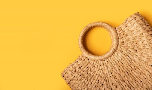 Эко сумка плетеной соломы или ротанга женская в деталях на желтой стене. плоская планировка сверху. концепция путешествия летняя стена