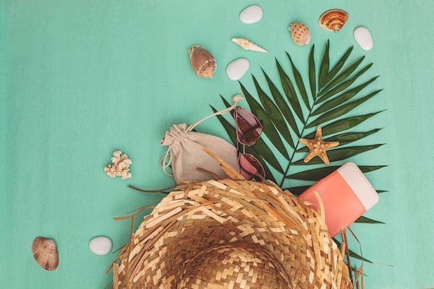 Плетеная летняя сумка с пляжными аксессуарами, солнцезащитные очки, косметика и ракушки с пальмовым листом на бирюзовом фоне, летний фон