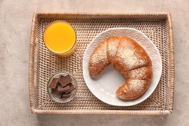 灰色のテーブルにおいしい新鮮な三日月形のロールとオレンジジュースのガラスが付いている籐のトレイ