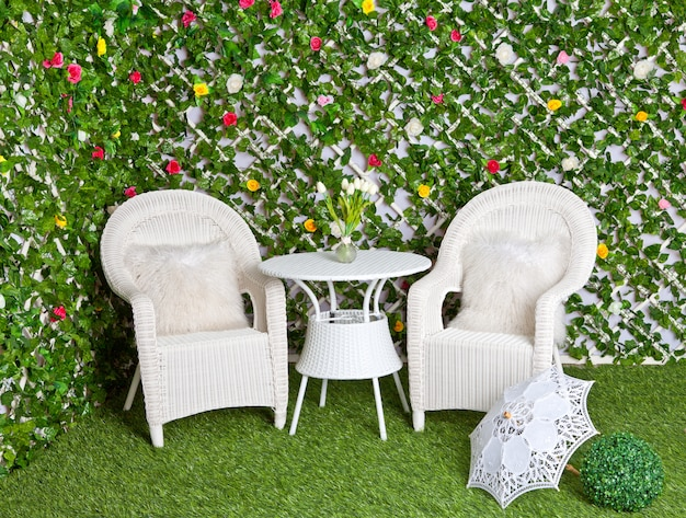 Wicker white furniture in the blooming garden
