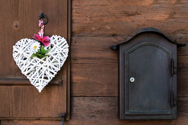 A wicker white heart with peonies and daisies hangs on a wooden shutter and a mailbox next to it.