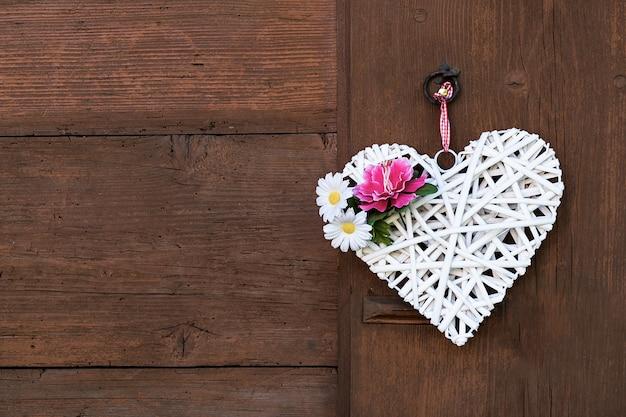 Плетеное белое сердце с пионом и маргаритками вися на деревянной стене.