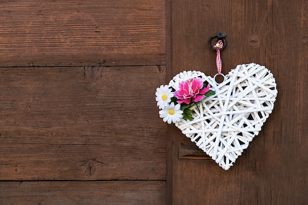 Wicker white heart with peony and daisies hanging on a wooden wall.