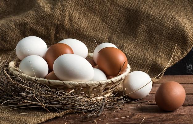 삼 베와 갈색 나무 바탕에 갈색과 흰색 계란 건초에 고리 버들 세공 나무 접시.