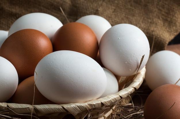삼 베의 배경에 갈색과 흰색 계란 고리 버들 나무 접시.
