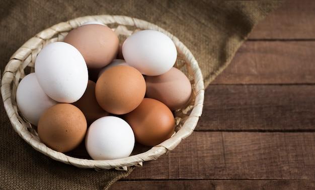 삼 베와 갈색 나무 바탕에 갈색과 흰색 계란 고리 버들 세공 나무 접시.