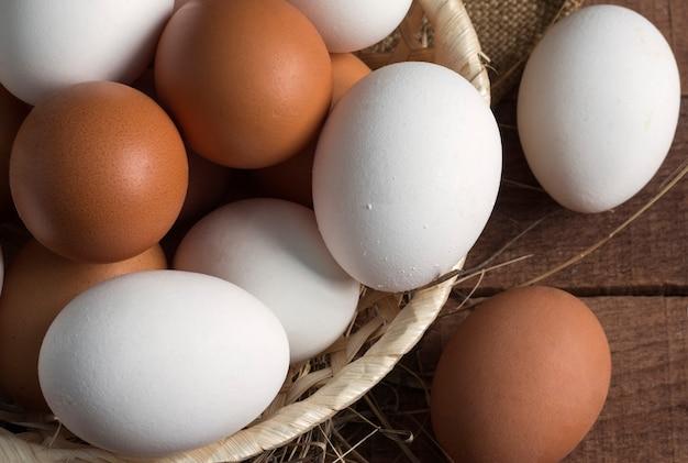 나무 배경, 평면도에 갈색과 흰색 계란 고리 버들 나무 접시.