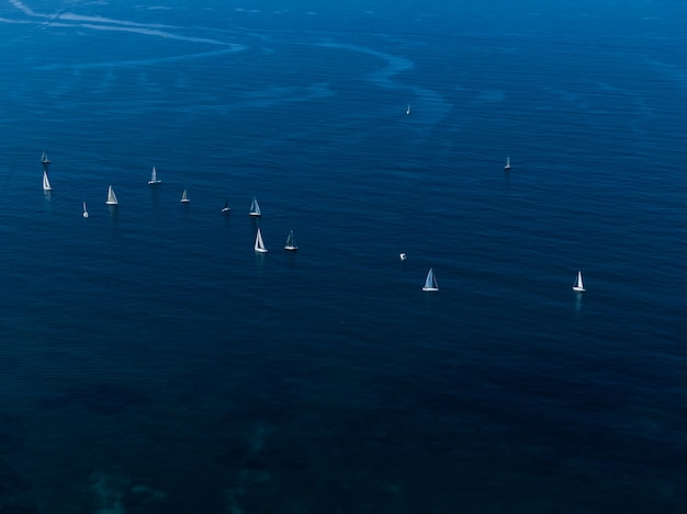 Wide aerial shot of small white sailboats floating in the ocean close to each other