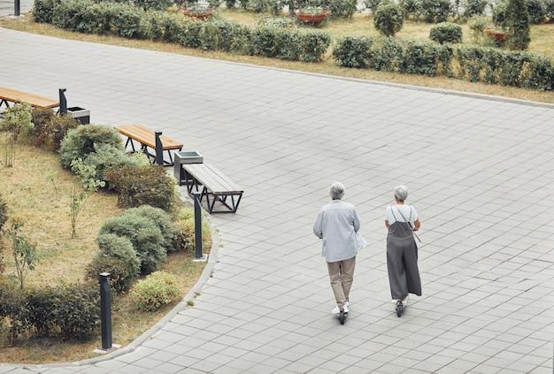 Широкоугольный вид сзади на современные пожилые пары, катающиеся на электрических скутерах в парке, копировальное пространство