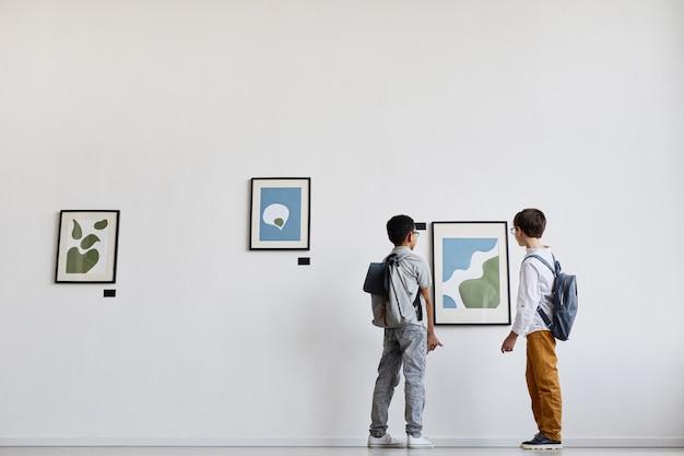 Широкоугольный вид сзади на двух школьников, смотрящих на абстрактные картины в галерее современного искусства, копировальное пространство