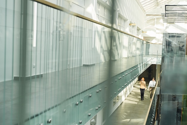 Wide angle background image of contemporary office building interior with glass and concrete, people walking on balcony, copy space