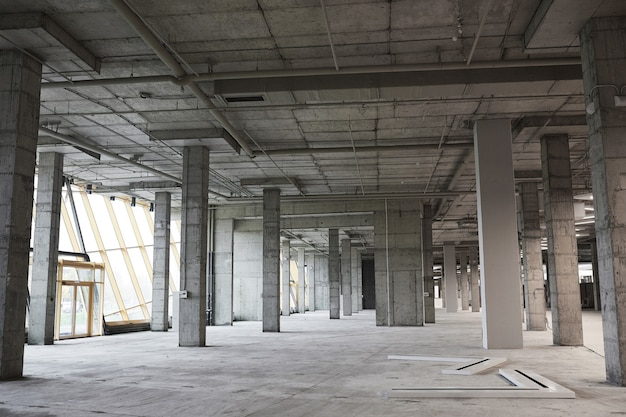 Wide angle background image of empty building under construction with concrete columns,