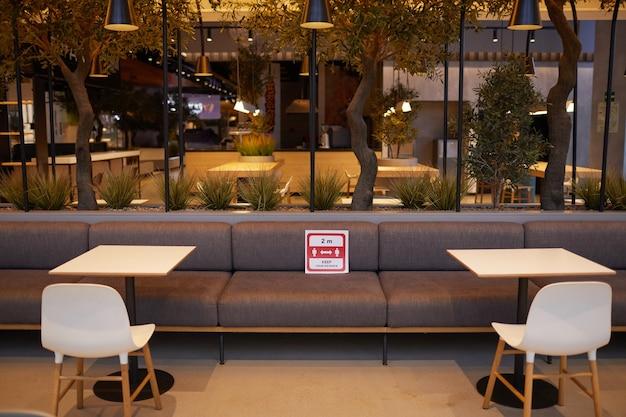 テーブルの間に赤い社会的な距離のサイン、コピースペースとショッピングモールの空のフードコートのインテリアの広角の背景画像