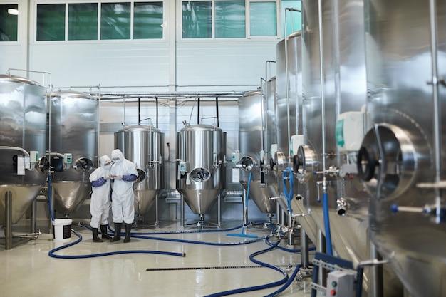 현대 화학 공장에서 보호복을 입은 두 명의 작업자가 있는 광각 배경, 복사 공간