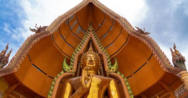 タイ、カンチャナブリのワットタムスア寺院にある黄金の大きな祝福の仏像の広角のクローズアップ。