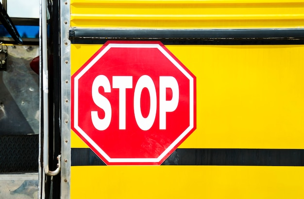밝은 노란색 주황색 스쿨 버스와 큰 빨간색 정지 신호의 광각 전면보기